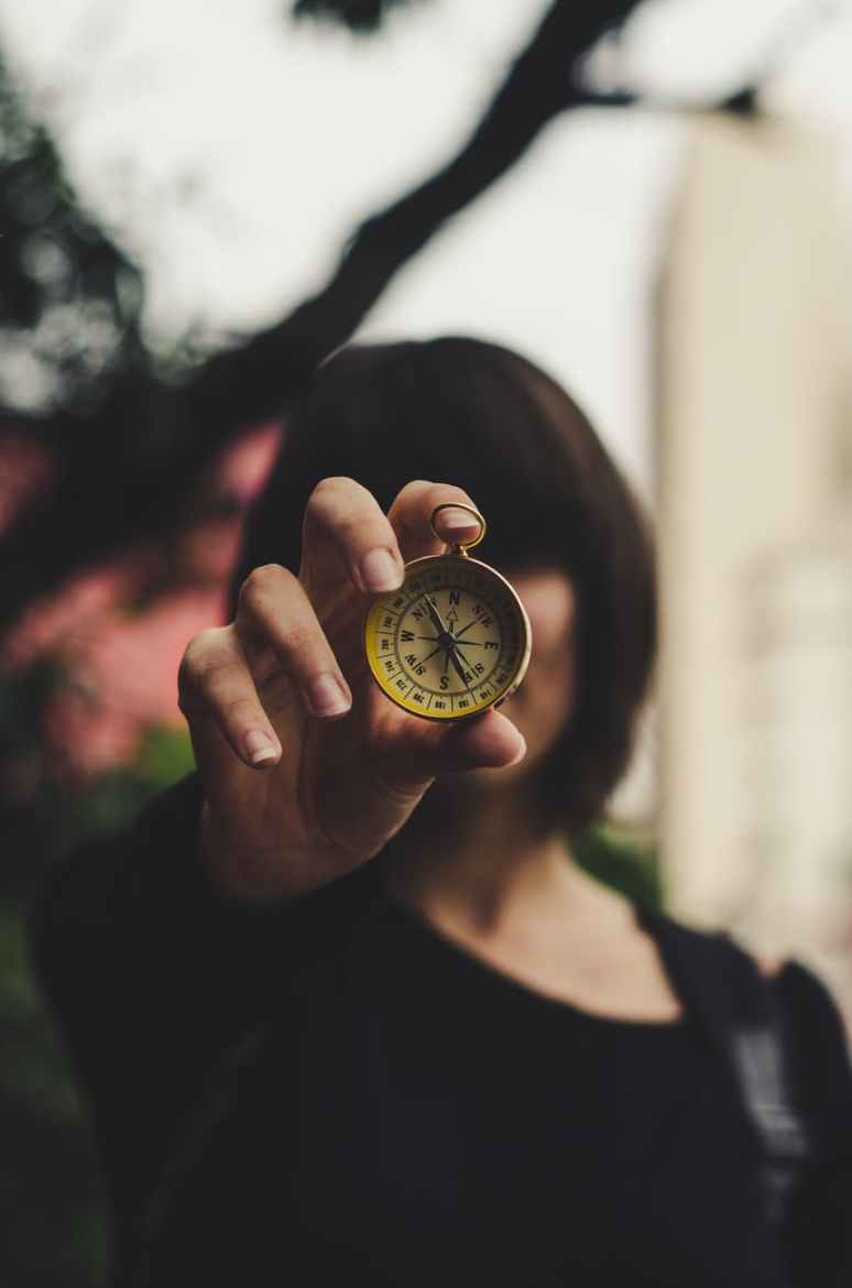 photo of woman holding compass